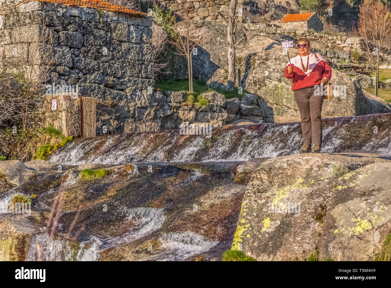 Seia / Portugal - 03 16 2019 :View of old woman taking pictures with mobile phone on stick, near the river with large granitic rocks, Estrela mountain - Stock Image