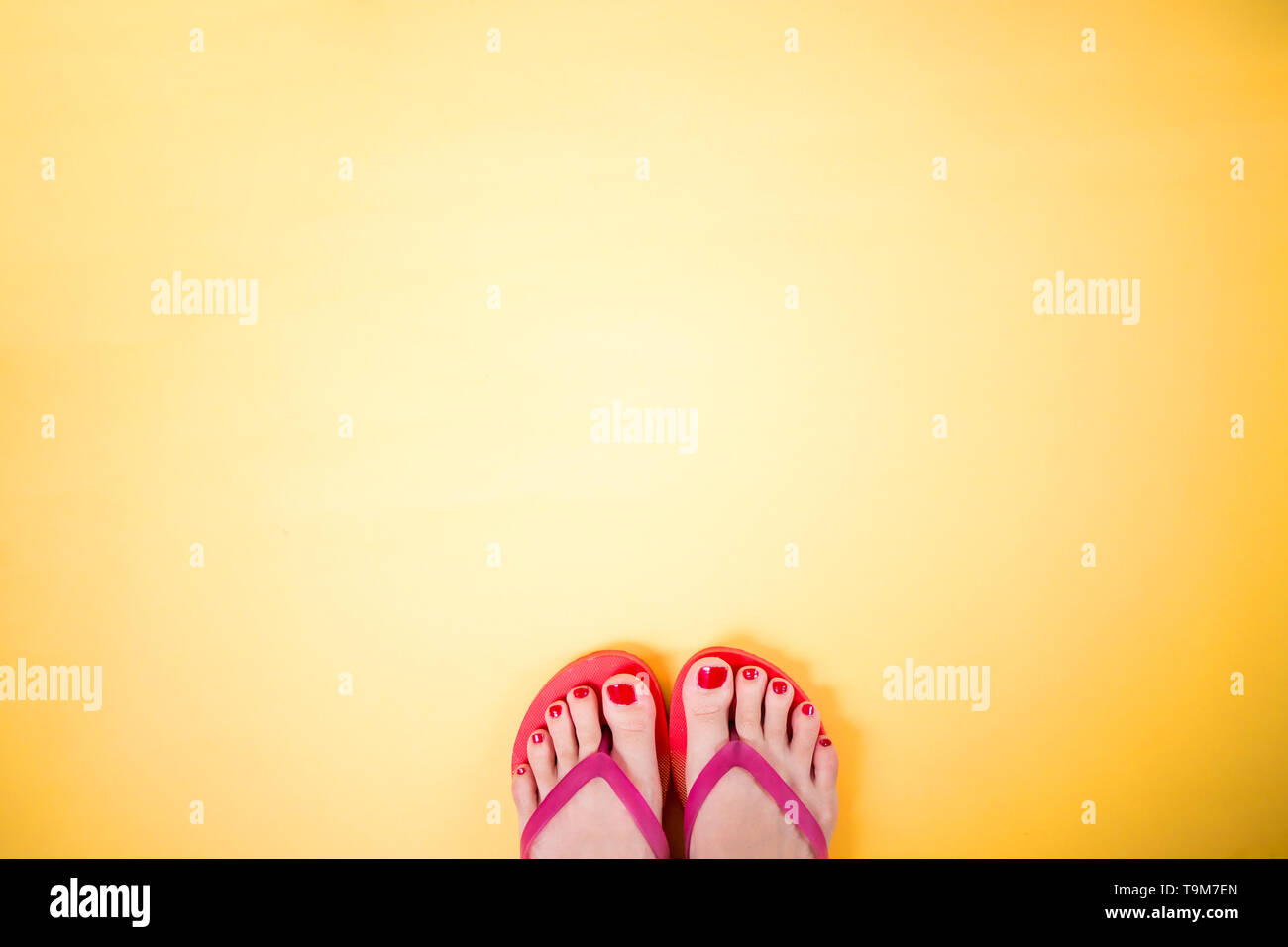 Woman's legs with red pedicure wearing pink flip flops on yellow background with copy space. Summer, vacation, travel, beach concept. - Stock Image