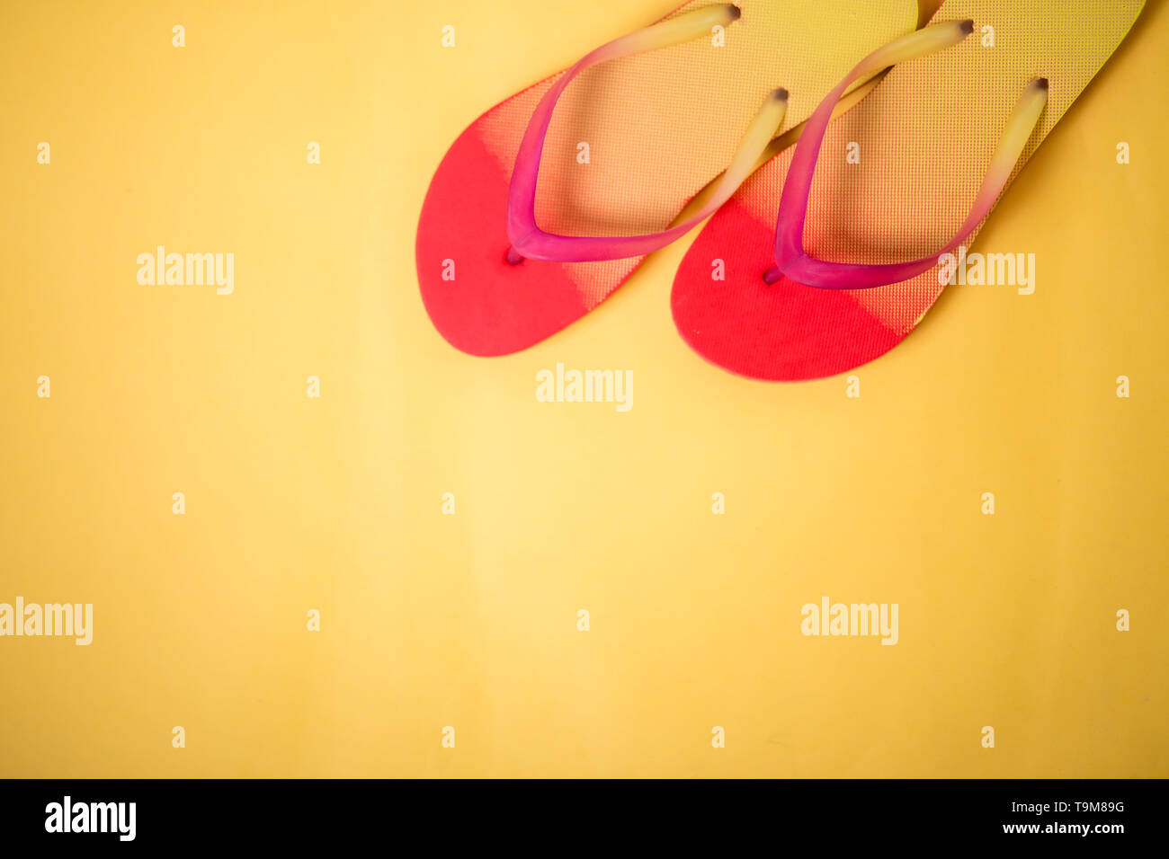 Coral pink sandals on yellow background with copy space. Flat lay, horizontal shot. Summertime, vacation, beach, shoes concept. - Stock Image