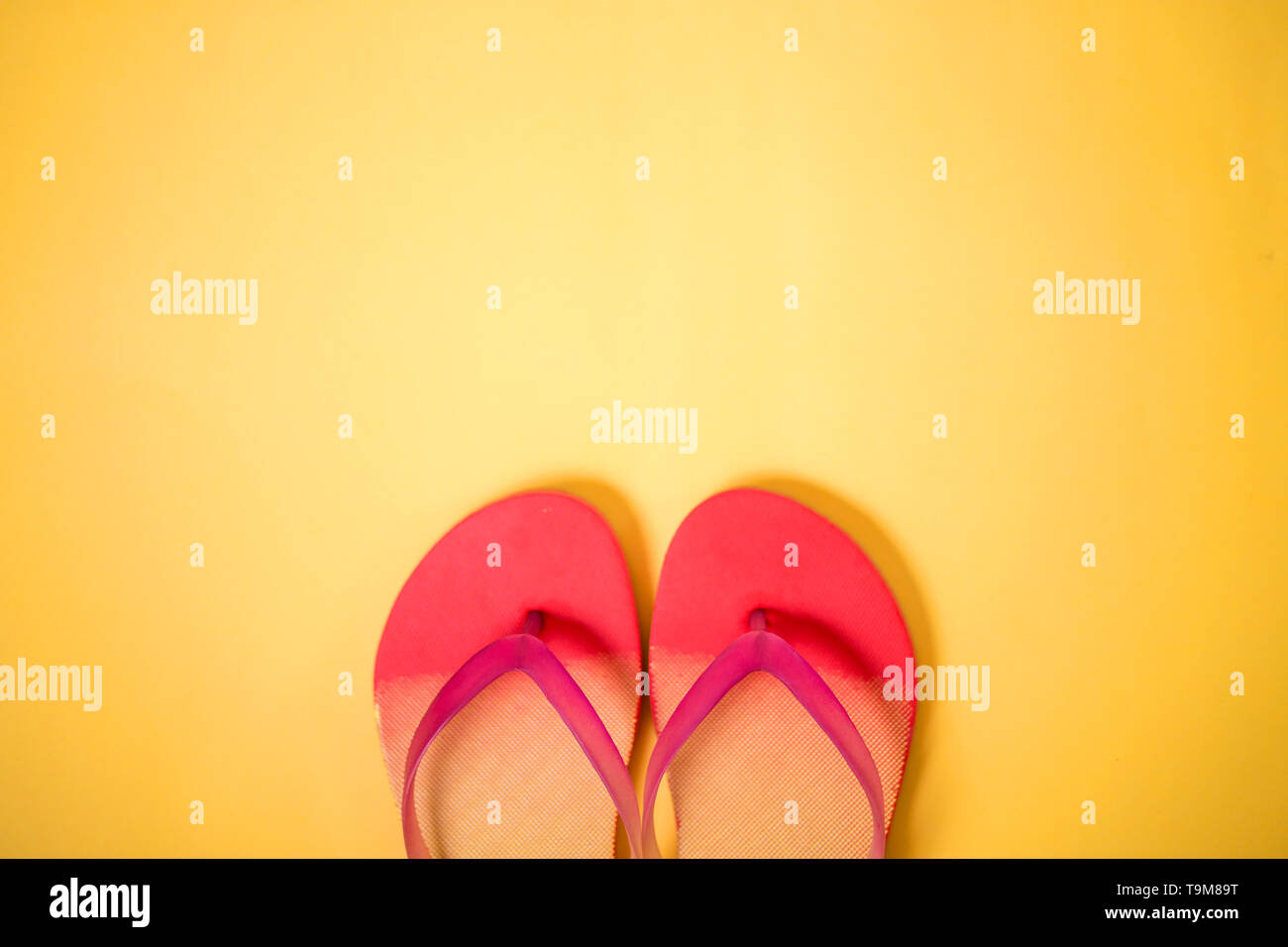 Coral pink flip flops on yellow background with copy space. Flat lay, horizontal shot. Summertime, vacation, beach, shoes concept. - Stock Image