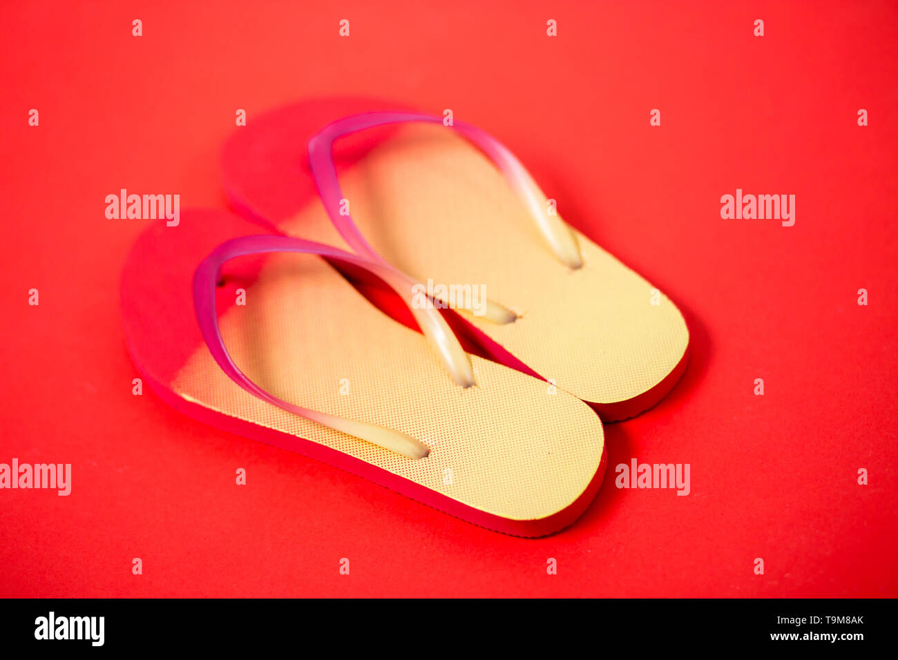 Yellow pink flip flops on red background. Flat lay, horizontal shot, close up. Summer, vacation, beach, shoes concept - Stock Image
