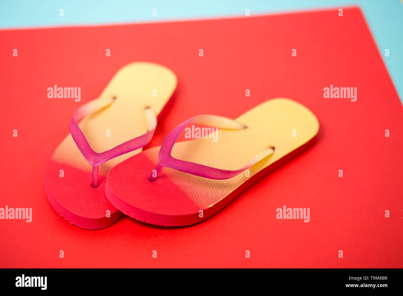 Pair of colorful flip flops on coral background. Summer, vacation, beach, shoes, shop concept. Studio shot of pink yellow sandals. - Stock Image