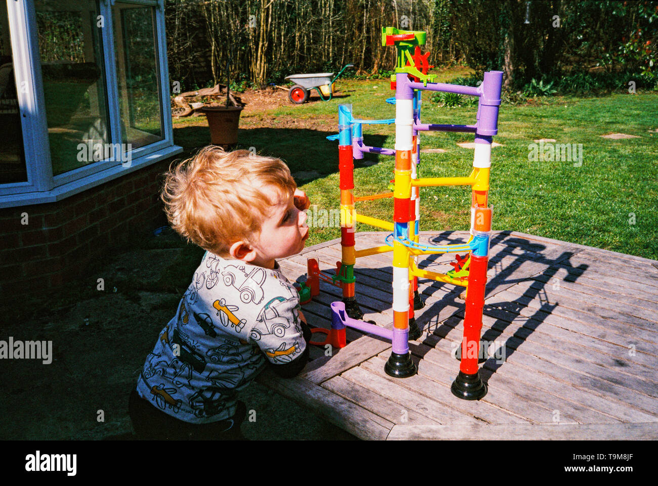 Two year old boy playing with a toy marble run. Medstead, Hampshire, England, Unite Kingdom. - Stock Image