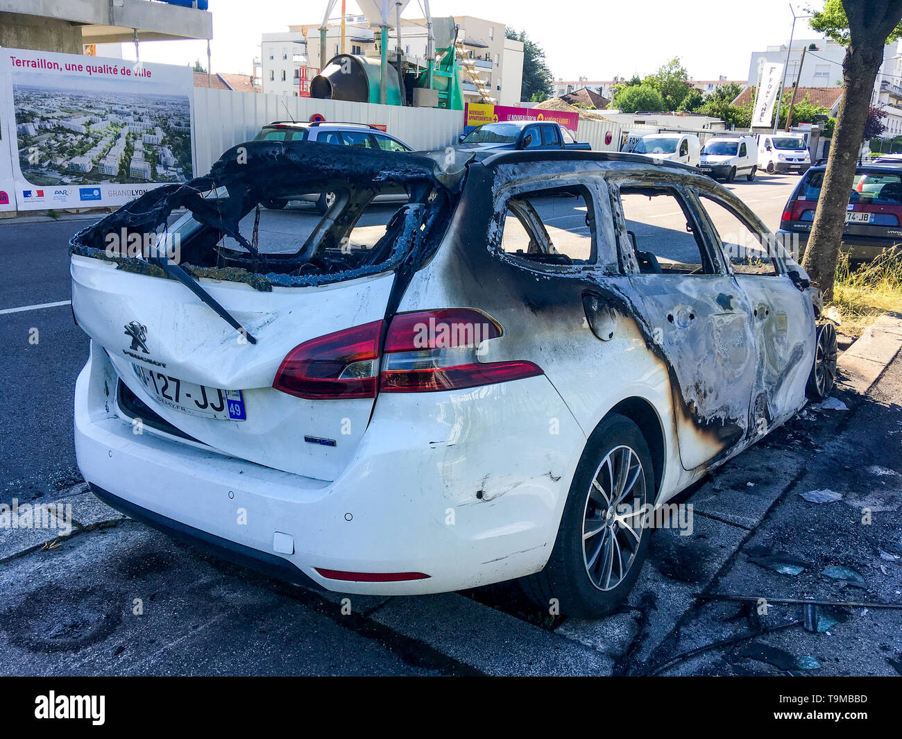 Street view, A burned car parked along a sidewalk, Bron, France - Stock Image