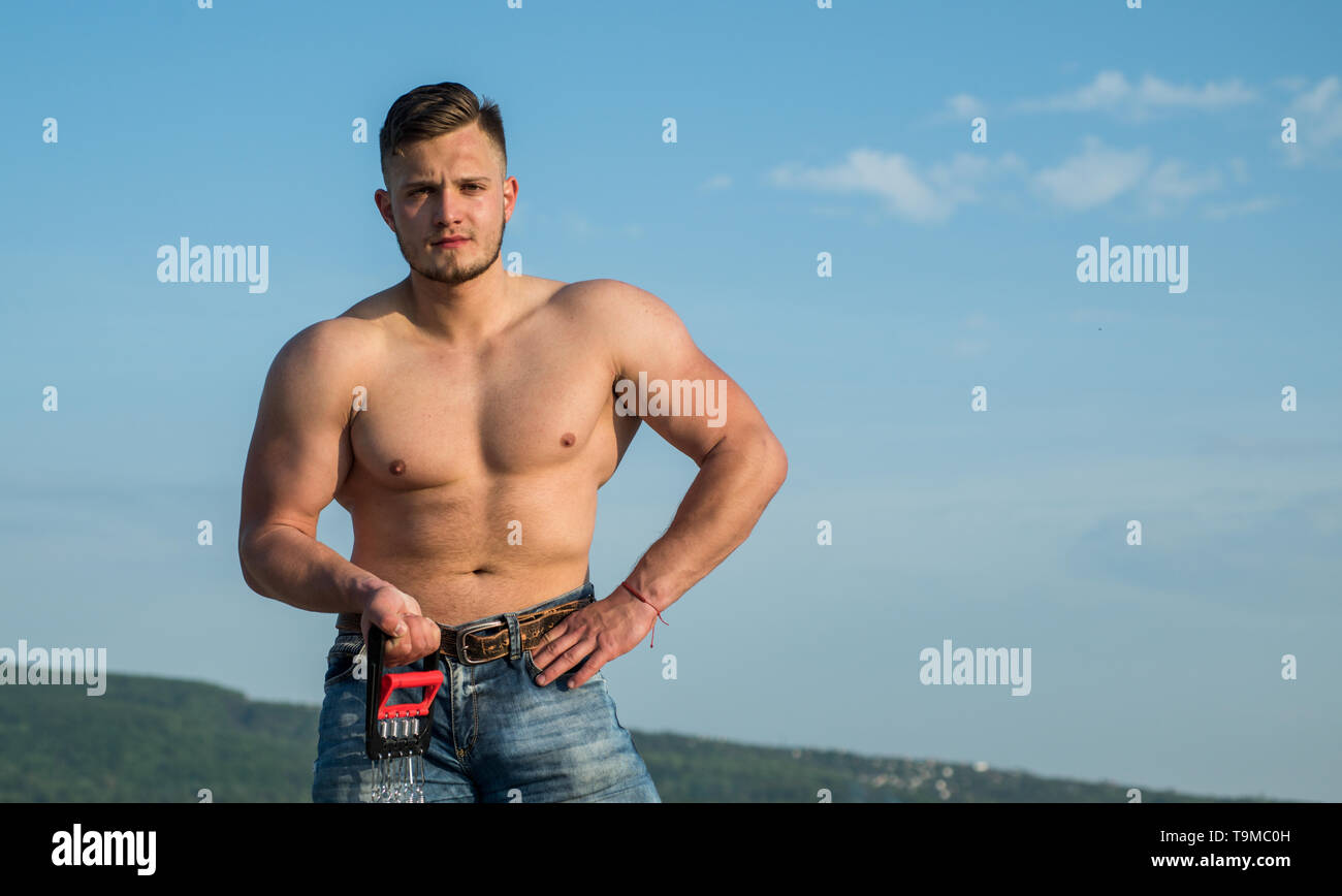 Athletic training. Athletic man with muscular torso on blue sky. Sportsman with athletic equipment outdoor. Athletic lifestyle and sport. Make - Stock Image