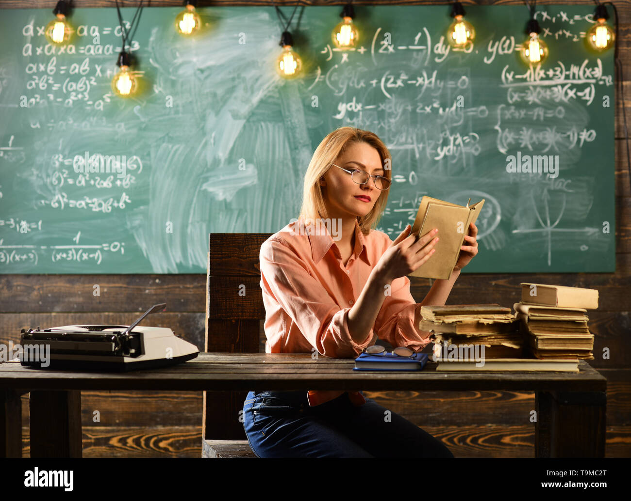 Private detective research. Information. Back to school and home schooling. Literature lesson with grammar book. Woman read love story novel in - Stock Image