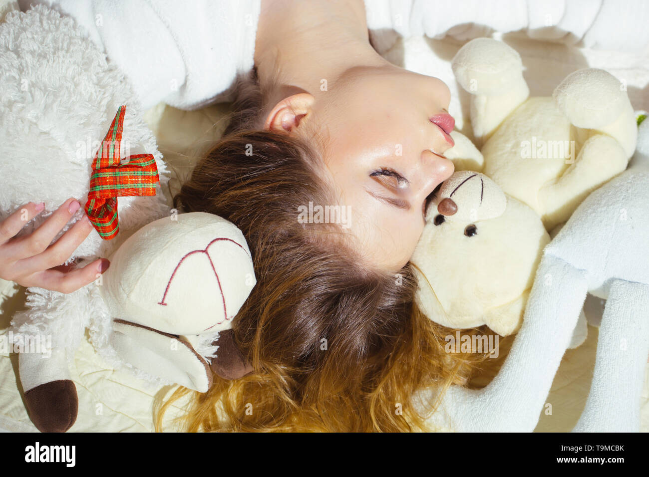 Beautiful girl with curly hair sleeping in bed. Pretty young woman hugging toy in sleep. Sweet dreams - Stock Image