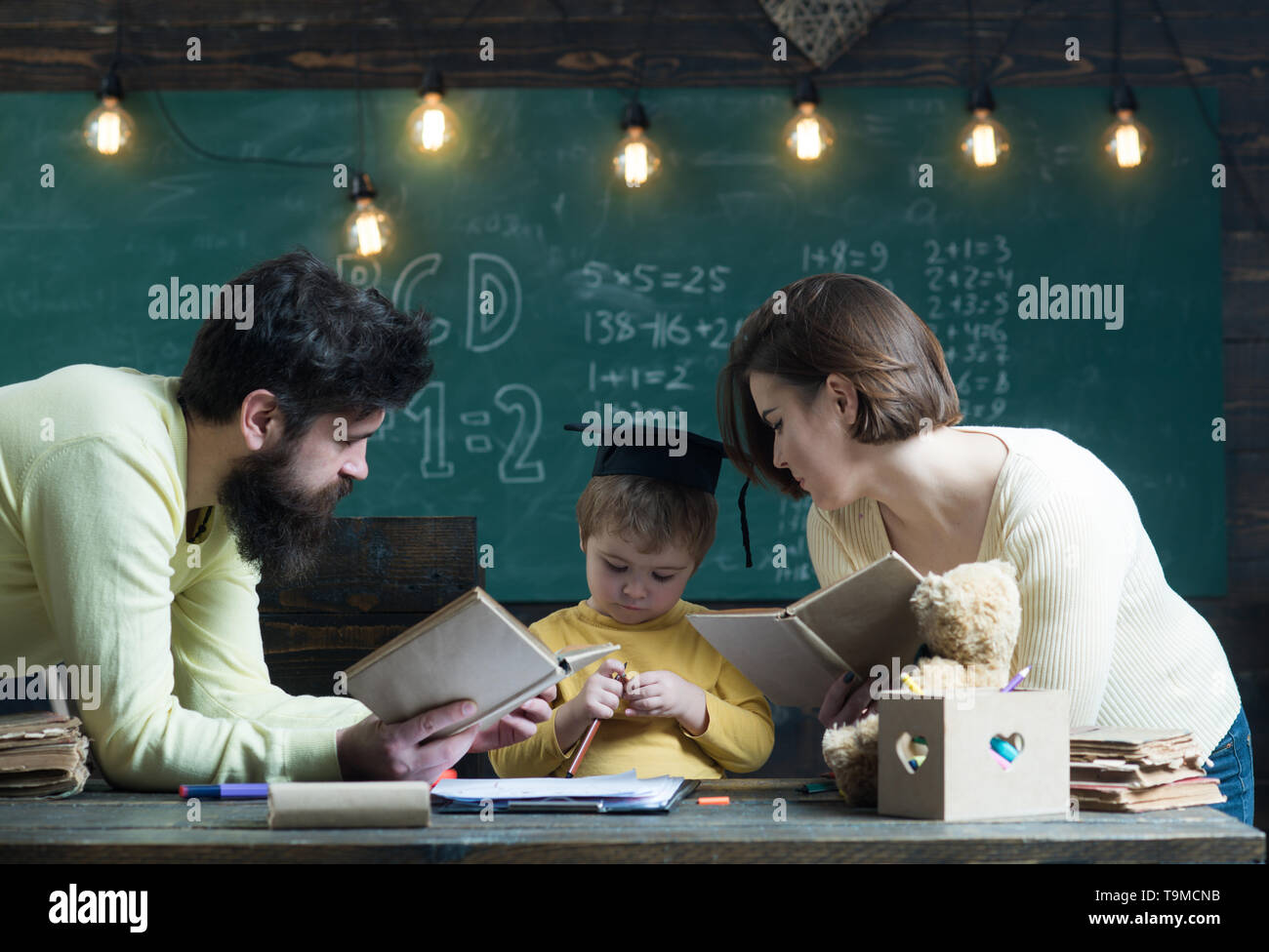 Homeschooling concept. Father and mother reading books, teaching their son, chalkboard on background. Family cares about education of their son. Boy - Stock Image