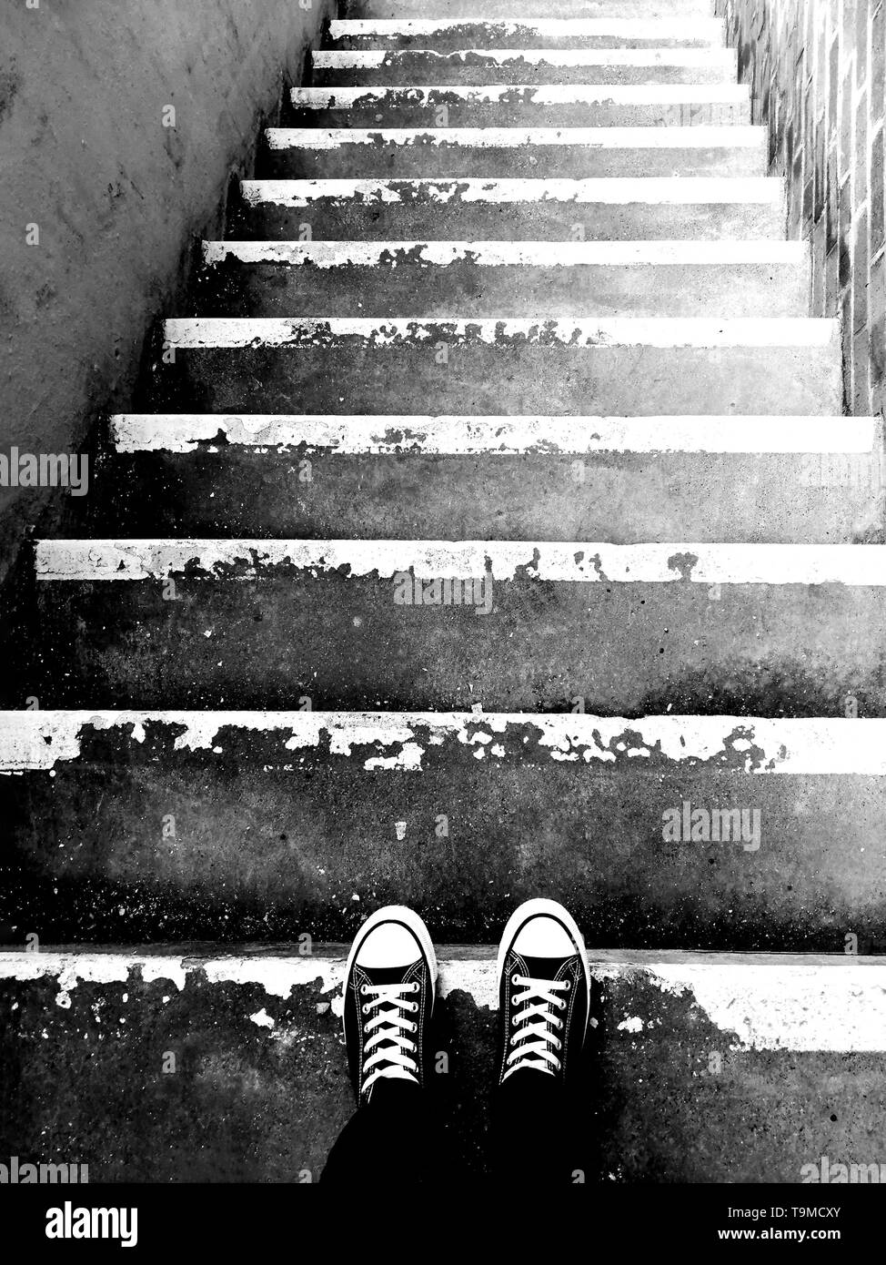 Feet at the top of stairs perspective from top to bottom. - Stock Image