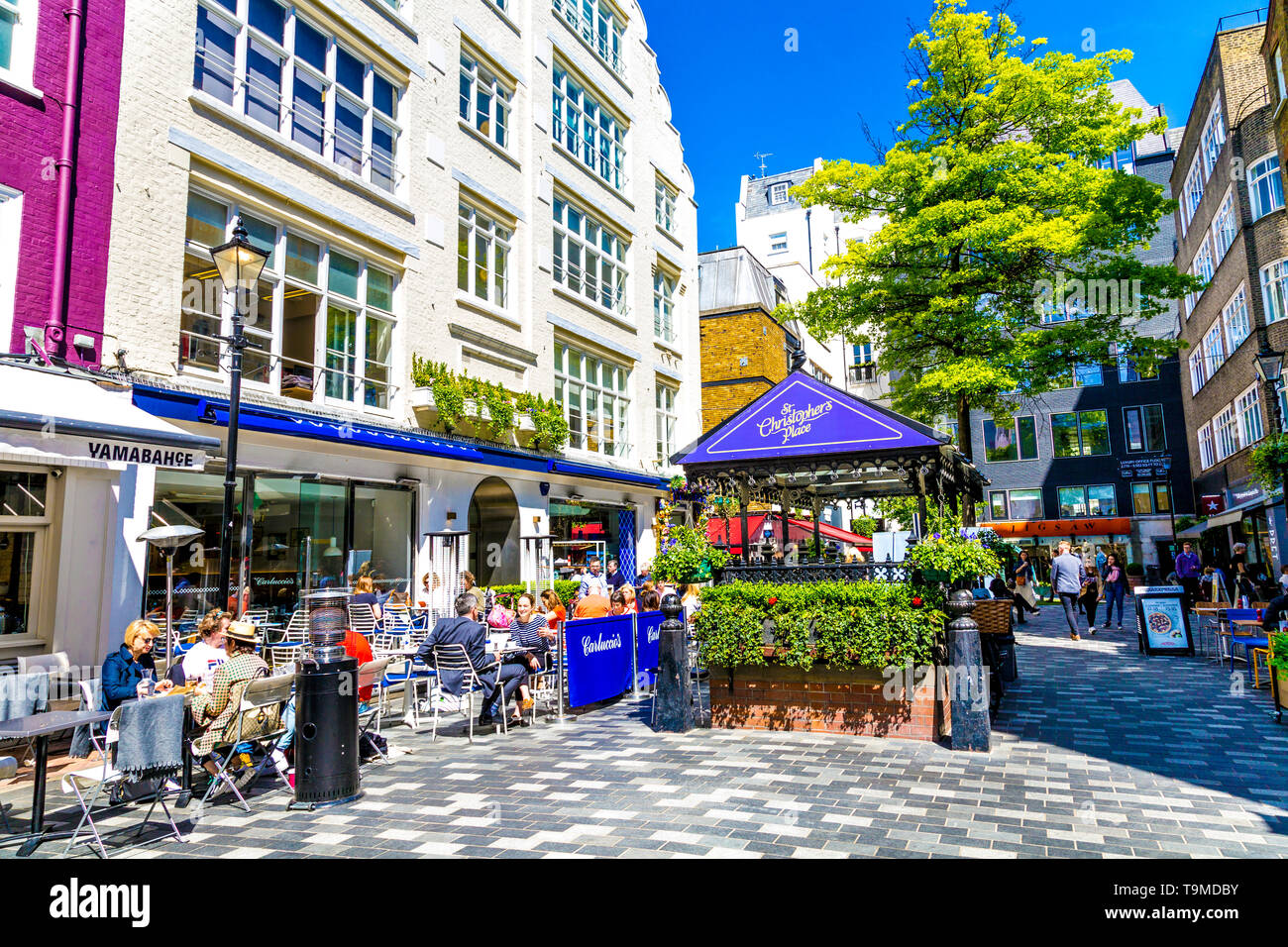 People eating at al fresco restaurants in St Christopher's Place, London, UK - Stock Image