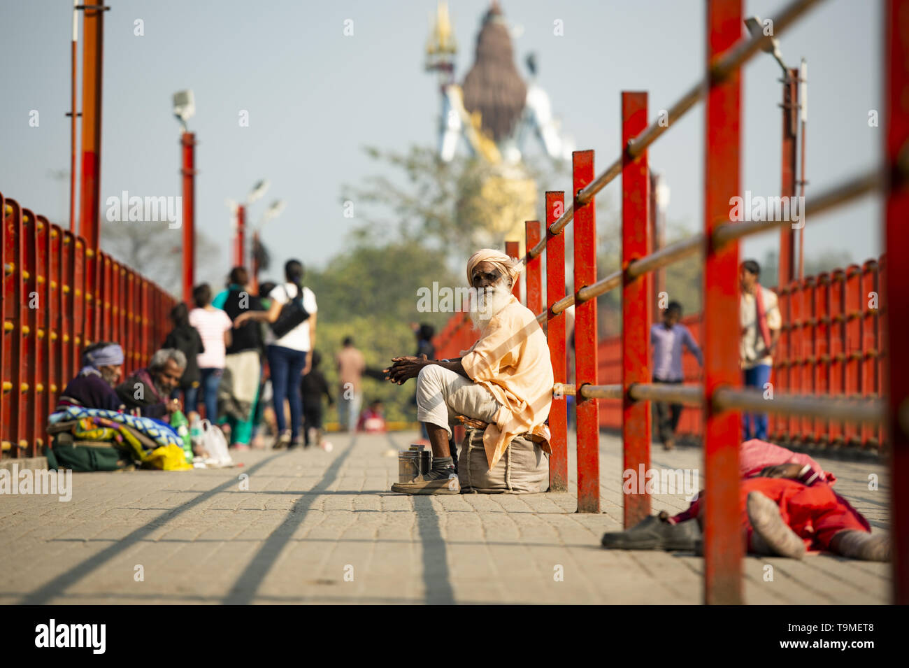 HARIDWAR - INDIA - 31 DECEMBER 2017. A poor Sadhu is asking for money in Haridwar, India. Blurred of Lord Shiva in the background. A Sadhu is a religi - Stock Image