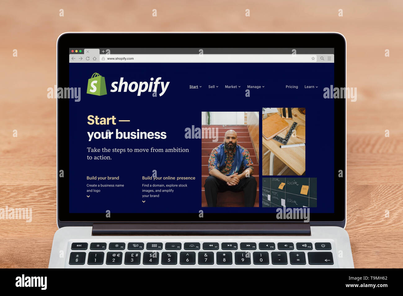 An Apple Macbook displays the Shopify website (Editorial use only). - Stock Image