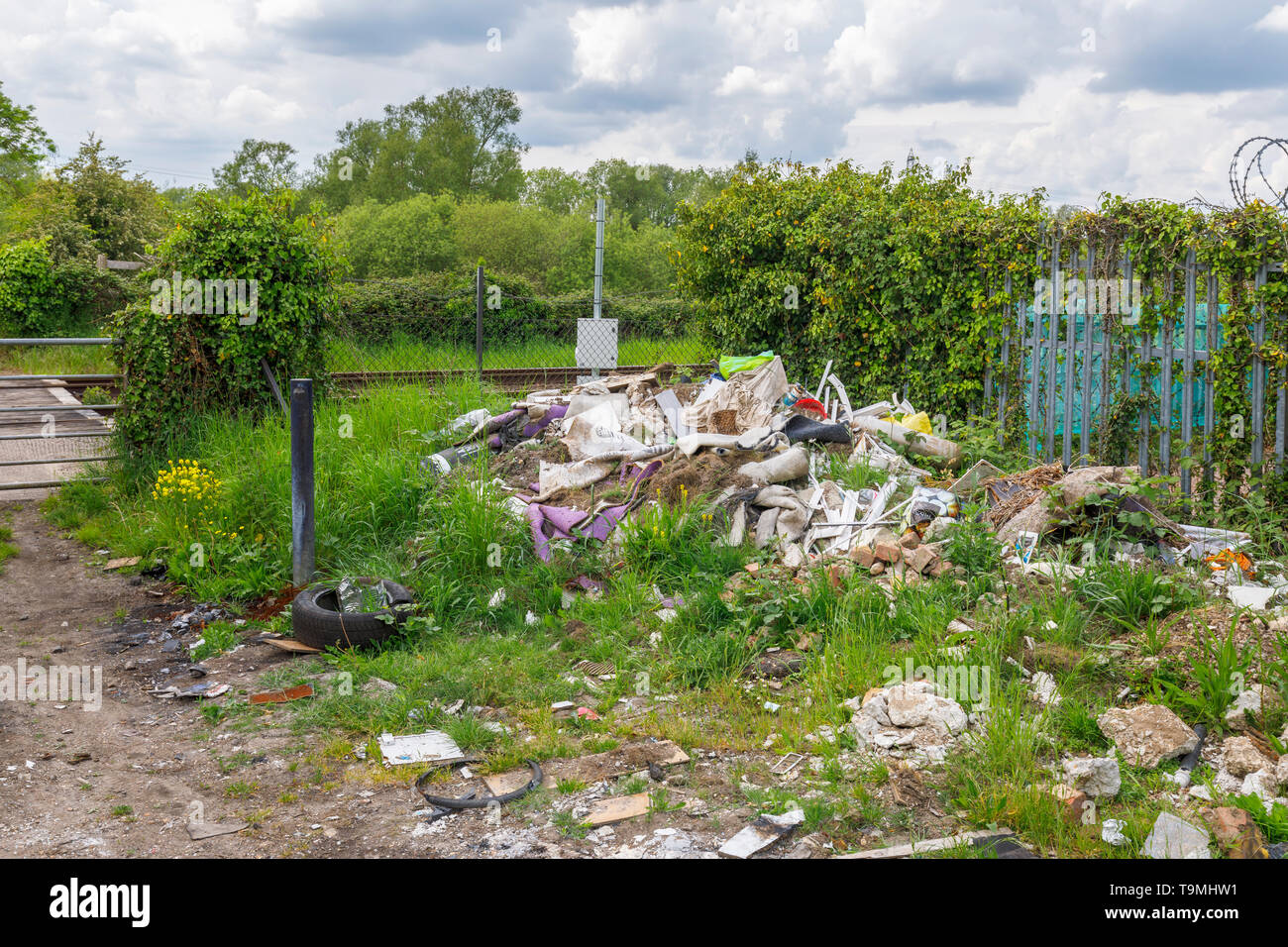 A pile of rubbish, rubble and trash from illegal fly tipping dumped beside a railway line in Nursling, Test Valley, Southampton, Hampshire, UK Stock Photo