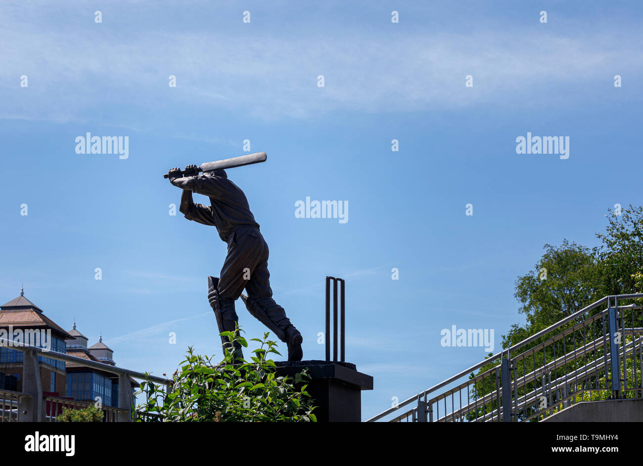 Bronze statue of cricket player Eric Bedser on Bedser Bridge, a footbridge on the Basingstoke Canal linking the WWF-UK headquarters to the town centre Stock Photo