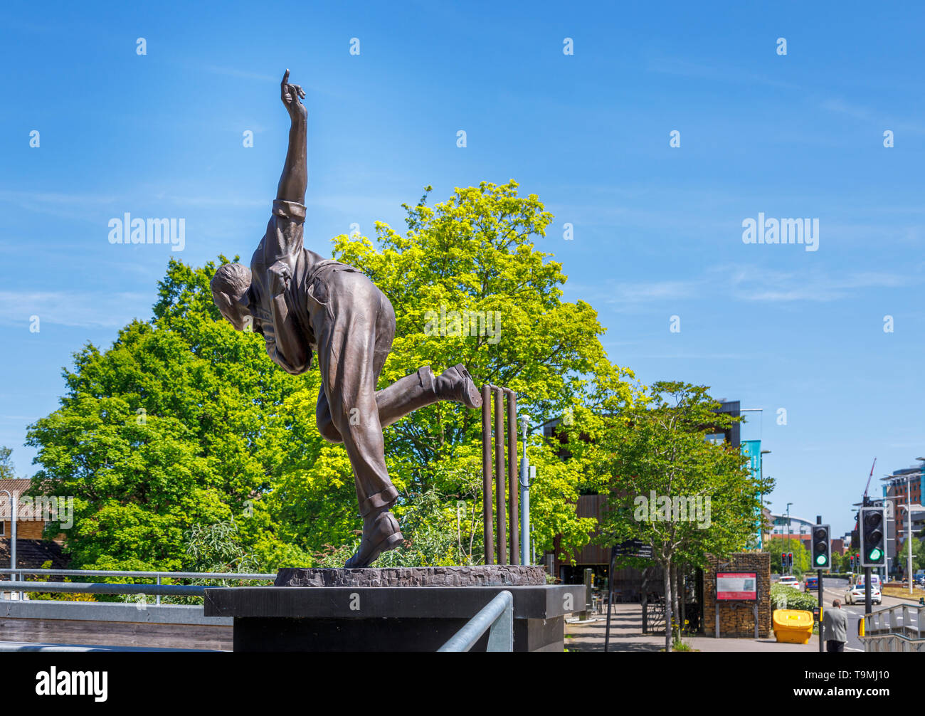Bronze statue of cricket player Sir Alec Bedser on Bedser Bridge, a footbridge on the Basingstoke Canal linking WWF-UK headquarters to the town centre - Stock Image