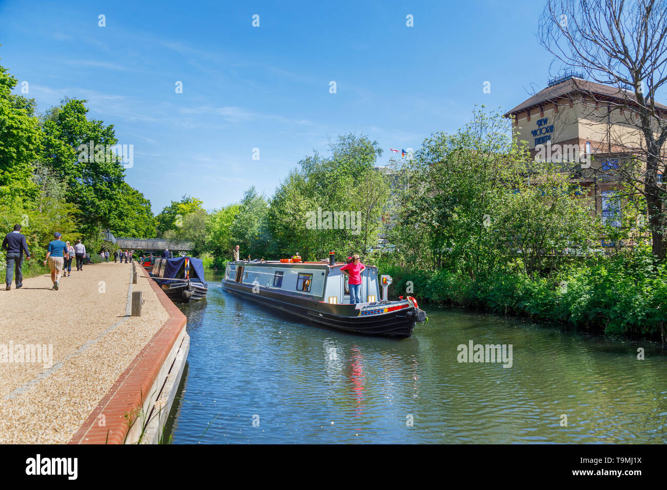 Narrowboat on the Basingstoke Canal passing through Woking town centre near the New Victoria Theatre, Surrey, southeast England on a sunny day - Stock Image
