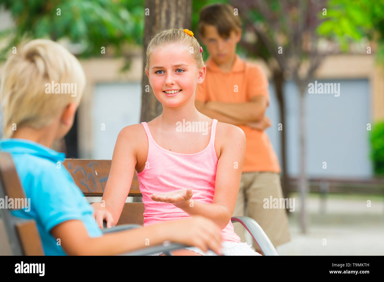 Kids are talking in the distance from their offended friend. - Stock Image