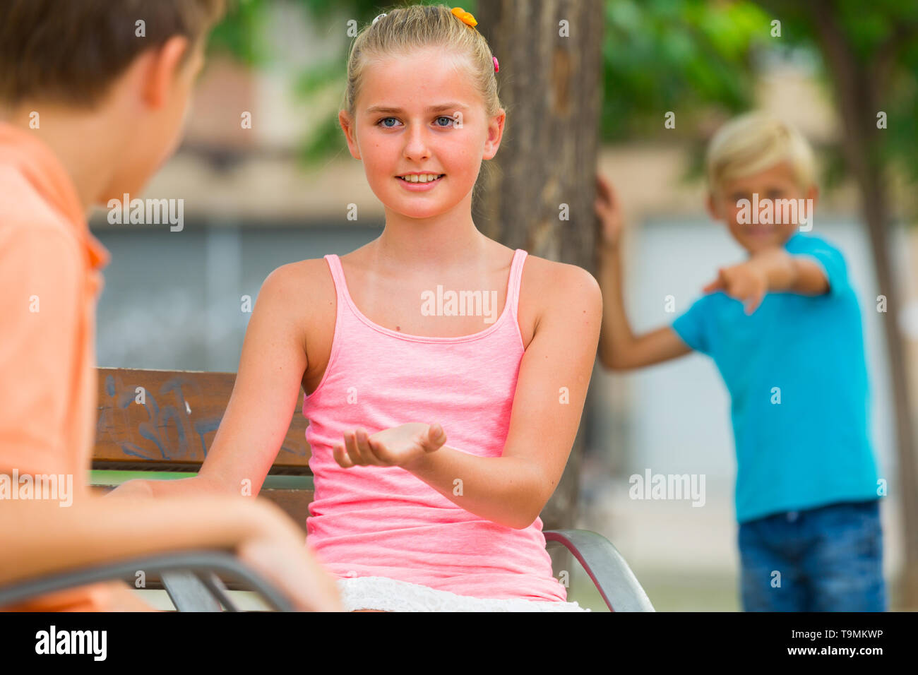 Boy is talking with girl in the distance from their offended friend. - Stock Image