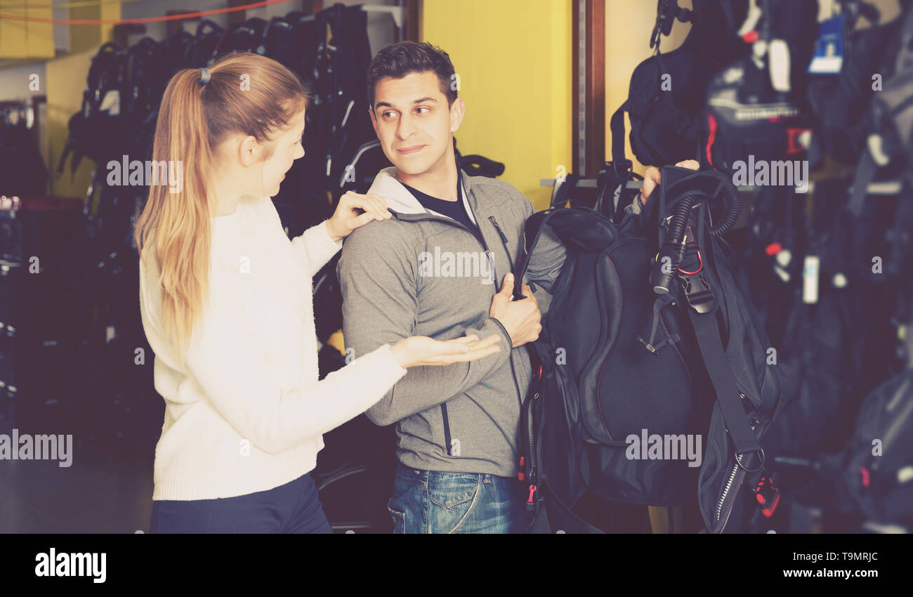 positive man is asking female seller about modern equipment for diving in the store. - Stock Image