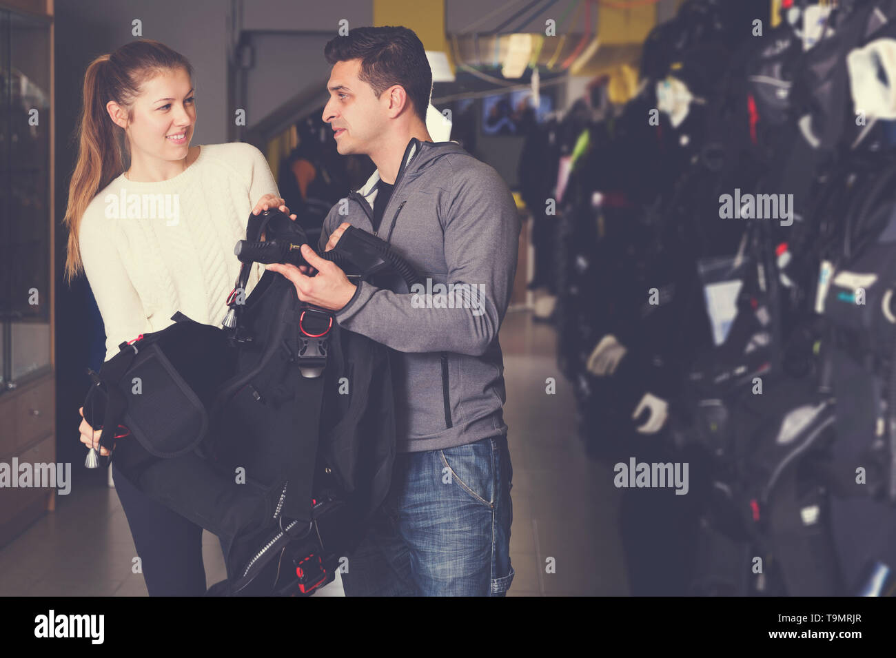 Man is asking female seller about modern equipment for diving in the store. - Stock Image