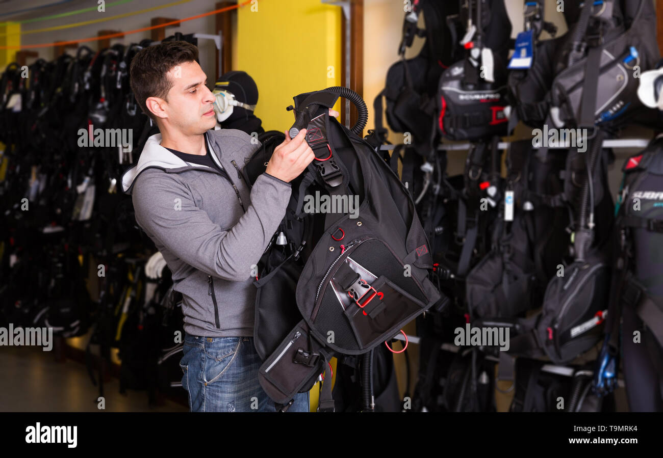 Sporty man is trying new diving vest in the diving store - Stock Image