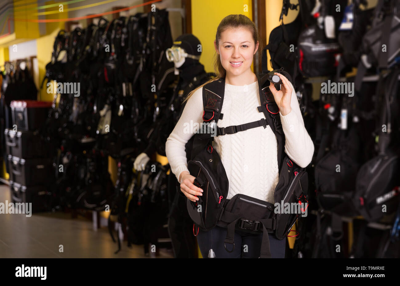 glad adult woman is standing in new equipment for diving in the store. - Stock Image