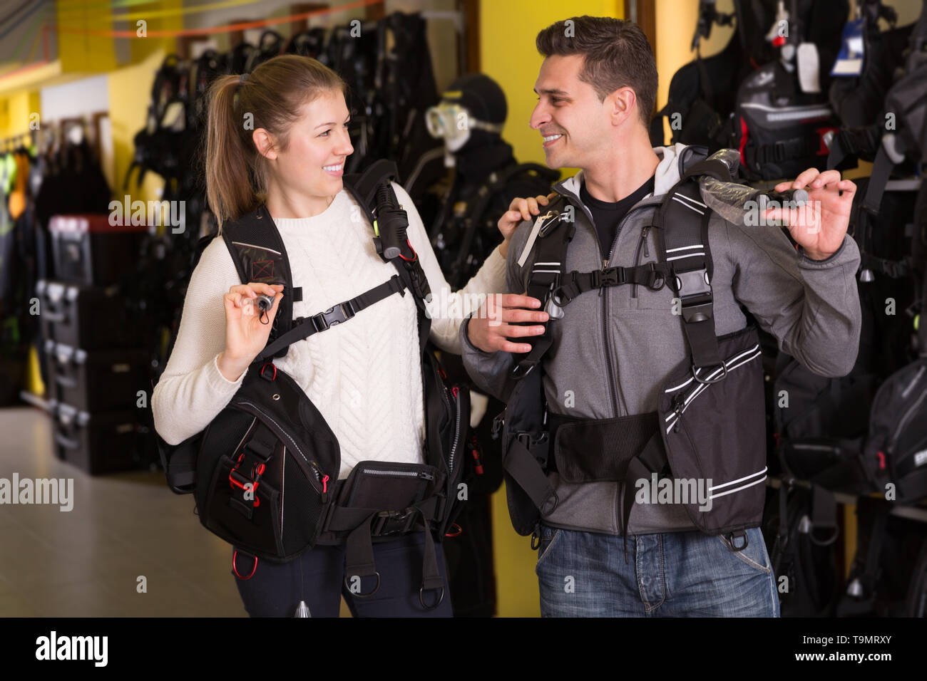 Male and woman standing in modern diving vest in the store - Stock Image