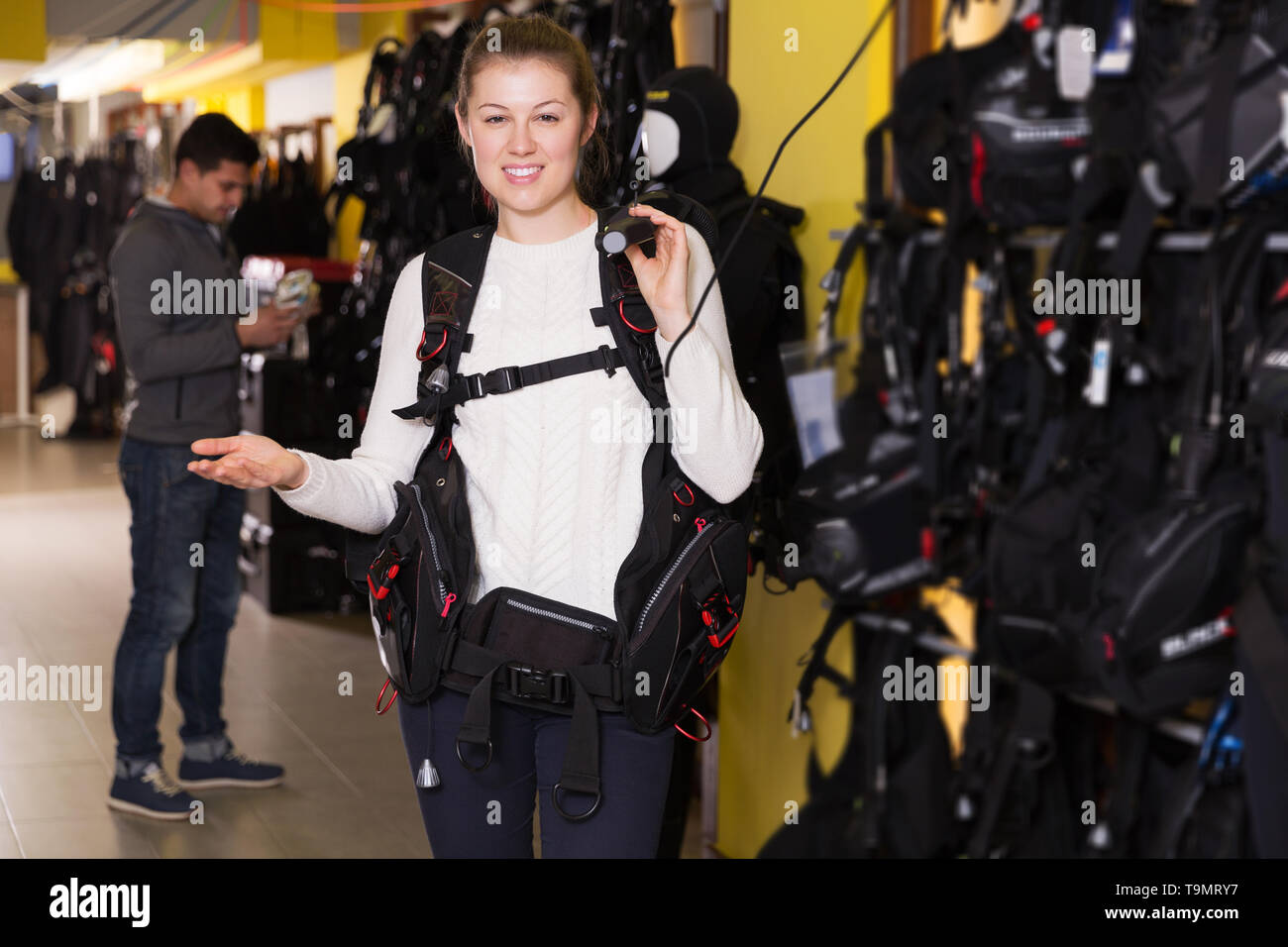 glad woman is standing in new equipment for diving in the store. - Stock Image