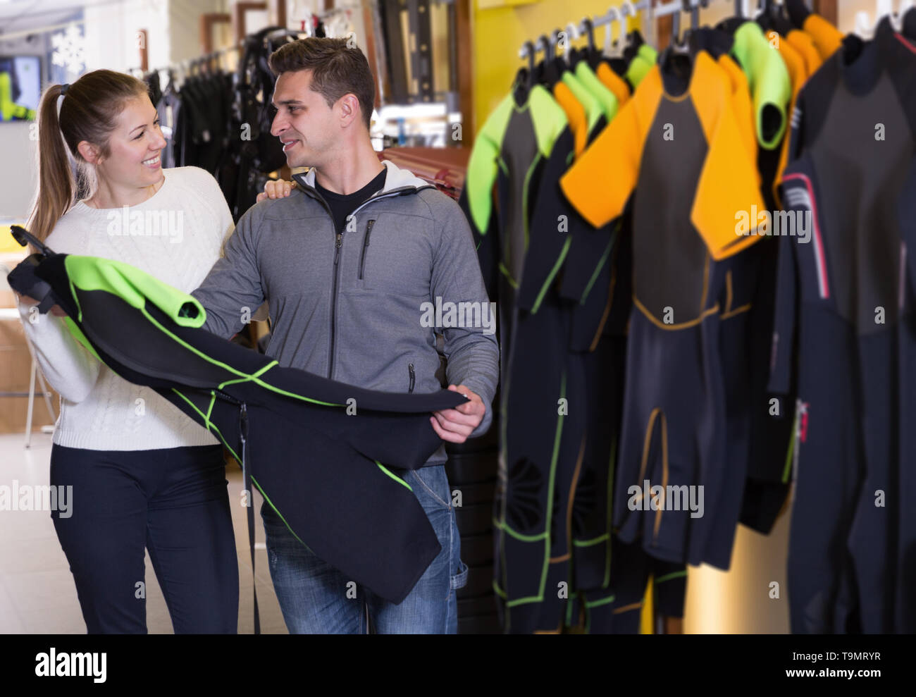 Girl seller is helping man choose new costume for diving in the store - Stock Image