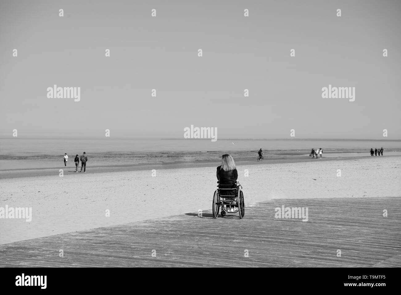 lonely disabled young woman on beach. Sunny summer day. - Stock Image