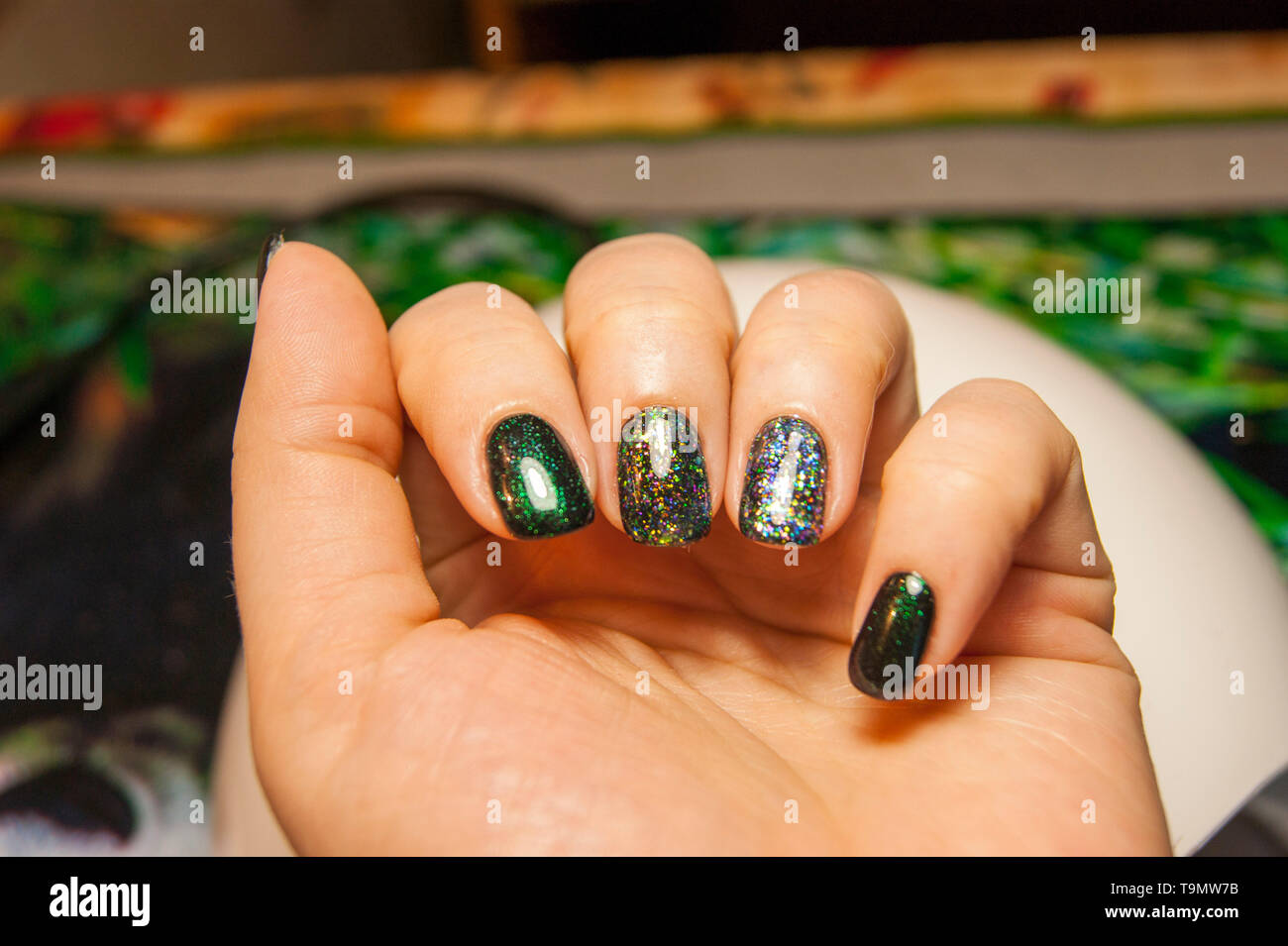 Women S Hands Beautiful Green Manicure Nail Polish On Nails Of Different Shades Of Green With A Slight Sheen And Large Shimmer Stock Photo Alamy