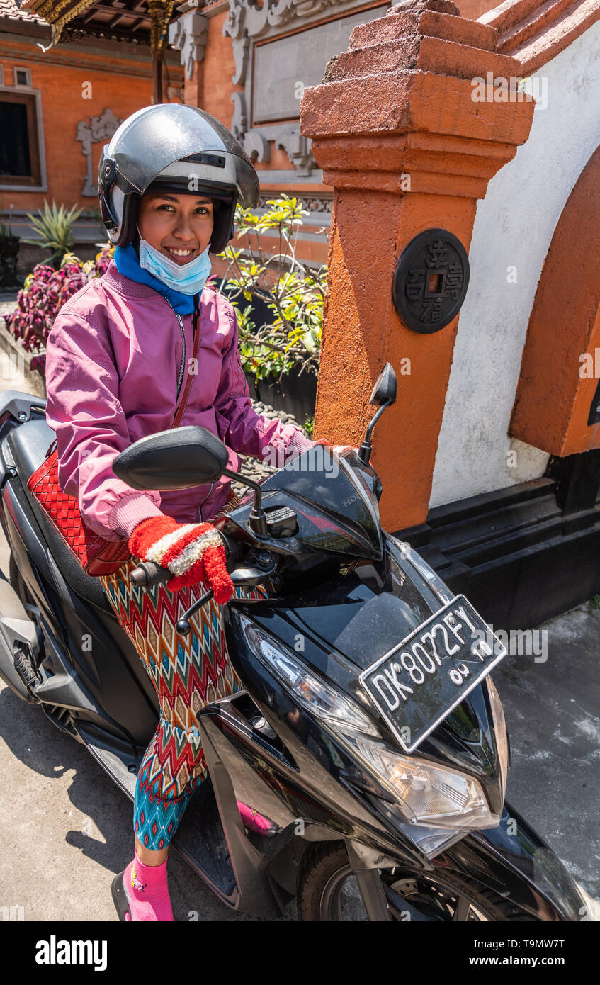 Bali, Indonesia - February 25, 2019: Young woman with helmet, sitting on black motorbike smiles. she wear pink vest and multicolor leggings. Back is r - Stock Image