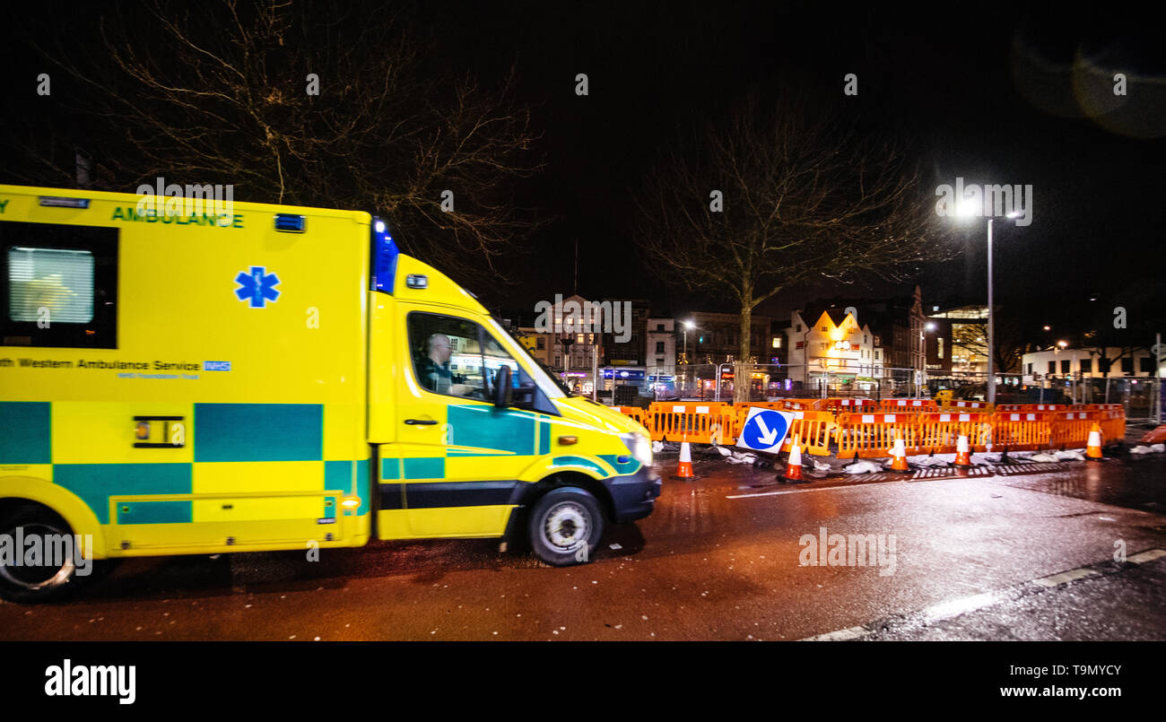 London, United Kingdom - Mar 5, 2017: Defocused Yellow NHS ambulance driving fast on the repaired with roadworks street in central london at night  - Stock Image