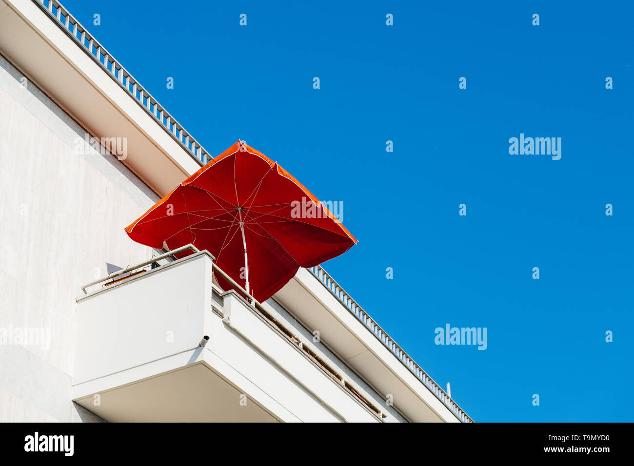 View from below of white modern balcony with red sunshade umbrella at a luxury real estate penthouse-apartment building - Stock Image