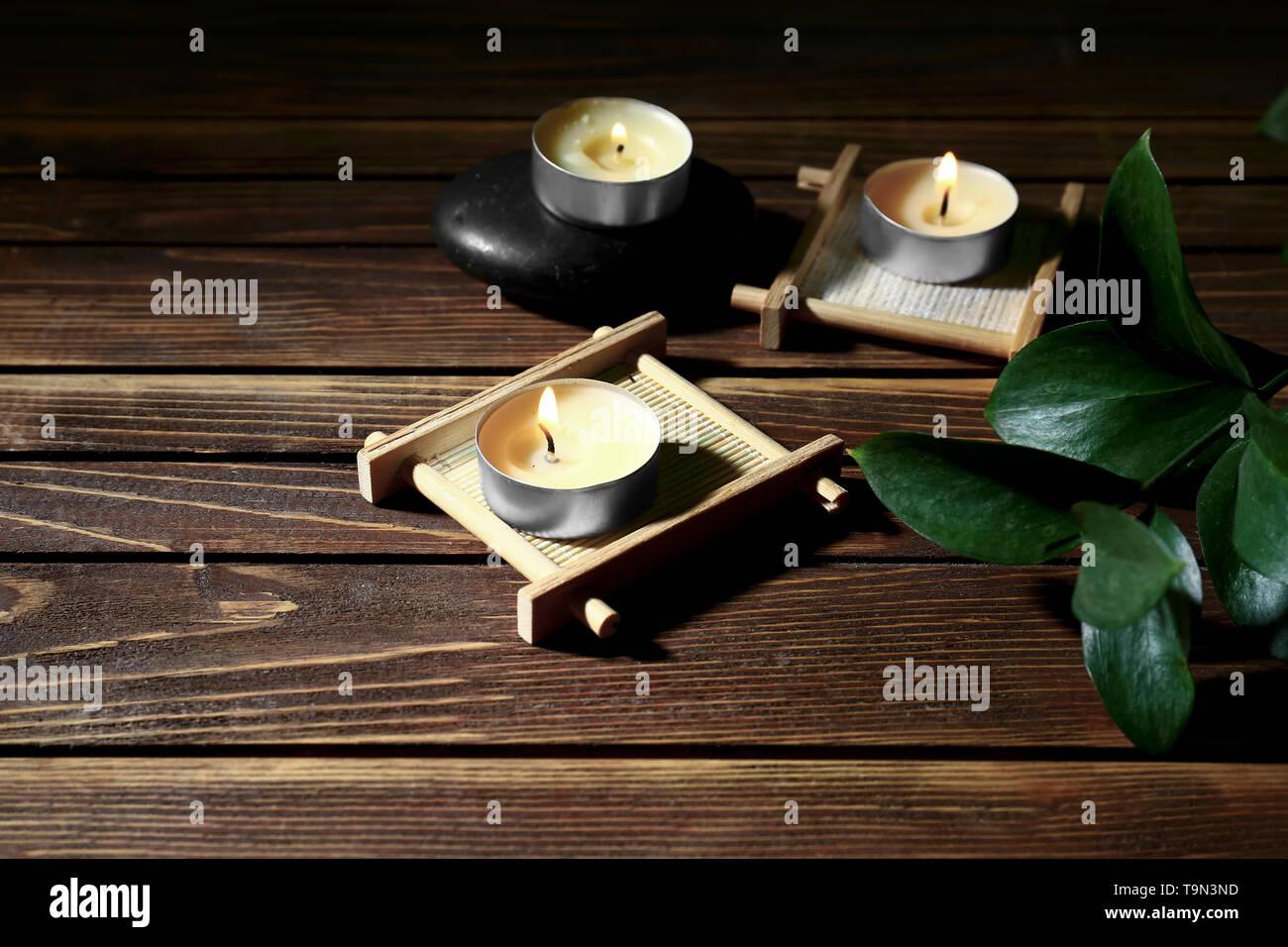 Burning candles on wooden background - Stock Image