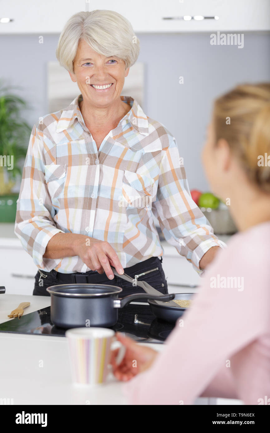 cheerful senior woman talking to daughter in kitchen - Stock Image
