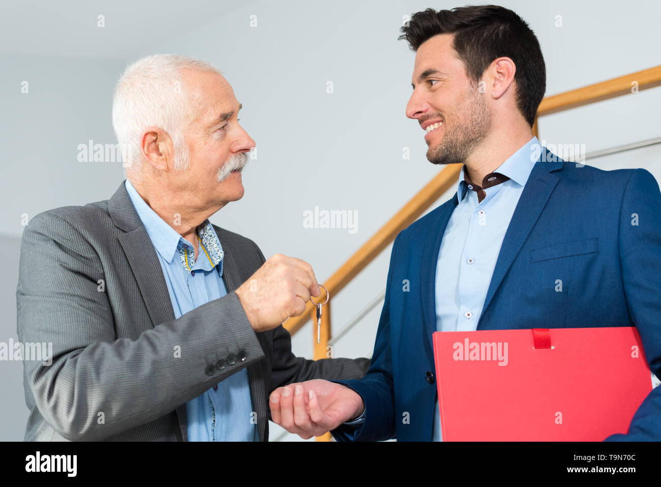 senior businessman passing keys to younger man - Stock Image