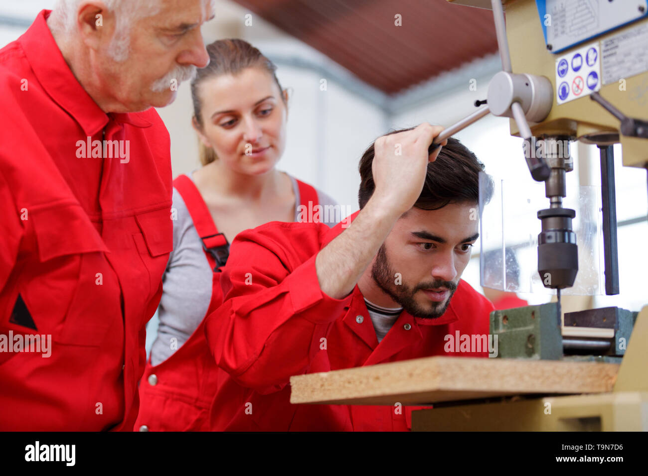 apprentice drilling a hole using a machine - Stock Image
