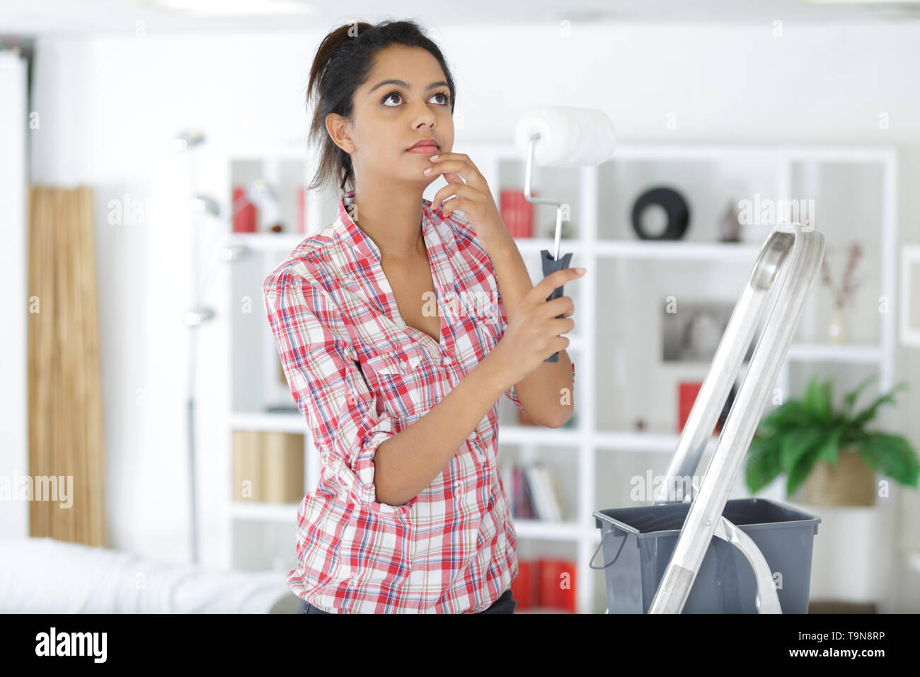 woman inspecting ceiling - Stock Image