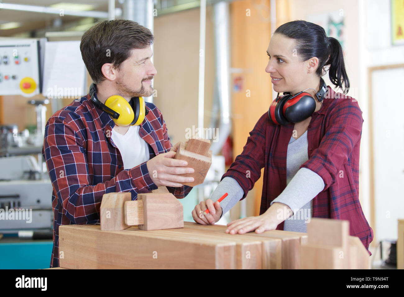 experienced carpenters in work clothes making a wooden furniture Stock Photo