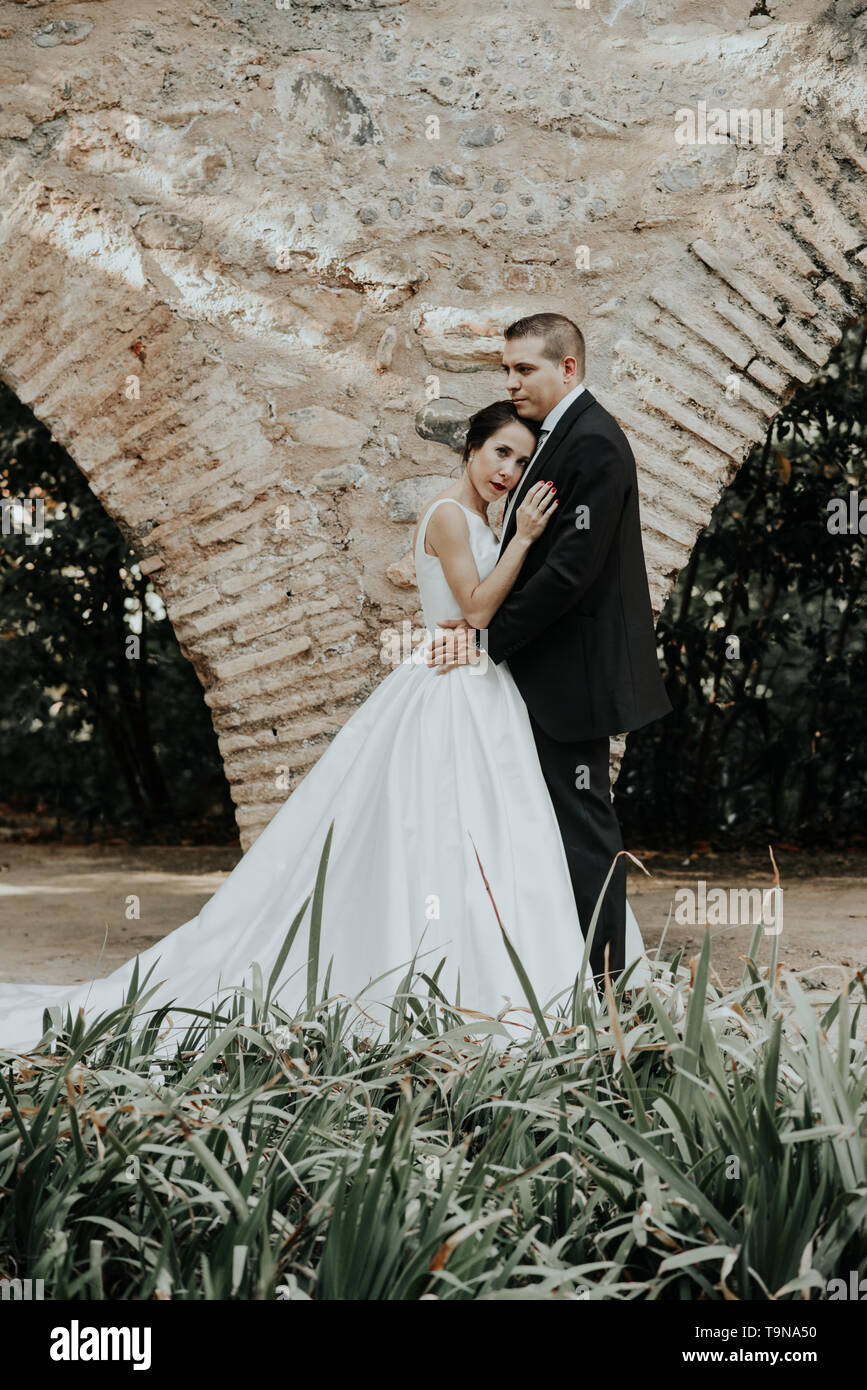 Bride and groom hug in the park. The bride leaned against the groom. Wedding day - Stock Image