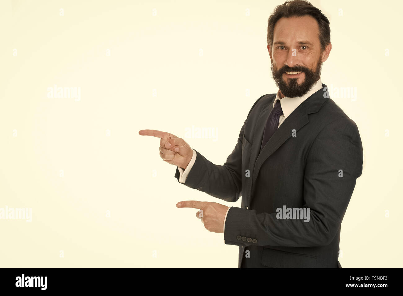 Pointing at copy space. Man pointing index fingers isolated on white. Man bearded mature in formal wear. Businessman or manager with beard and mustach - Stock Image