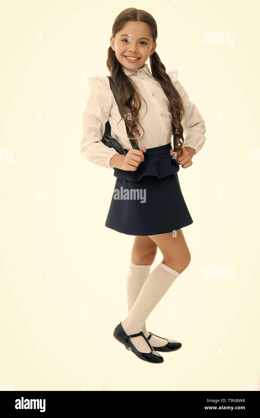 Learn how fit backpack correctly for school. Schoolgirl cute in formal uniform wear backpack. School backpack concept. Right and wrong ways to wear ba - Stock Image