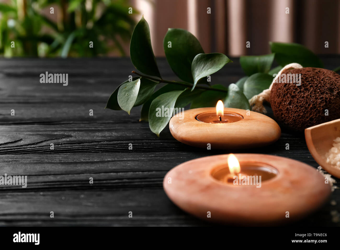 Beautiful spa composition with burning candles on dark wooden table - Stock Image