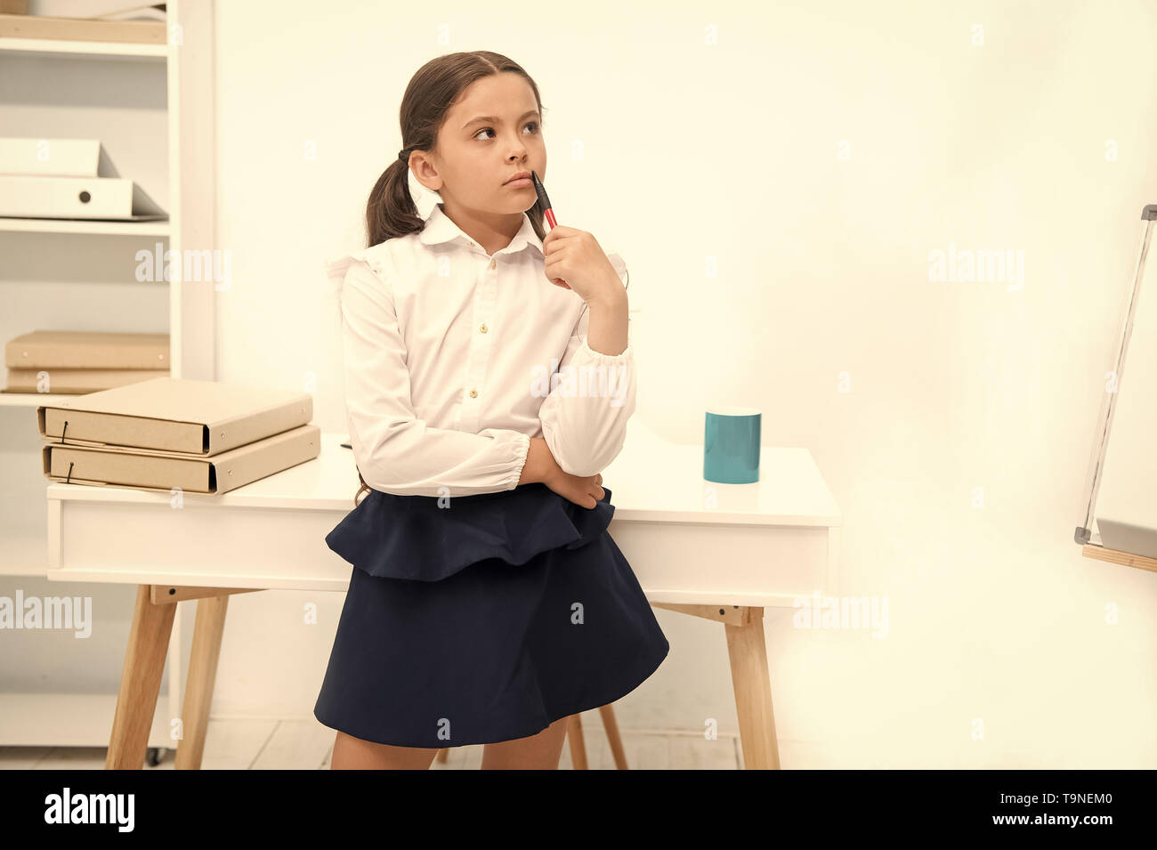 Focused on remembering. Child girl wears school uniform standing with remembering face expression. Schoolgirl smart child looks thoughtful white inter - Stock Image