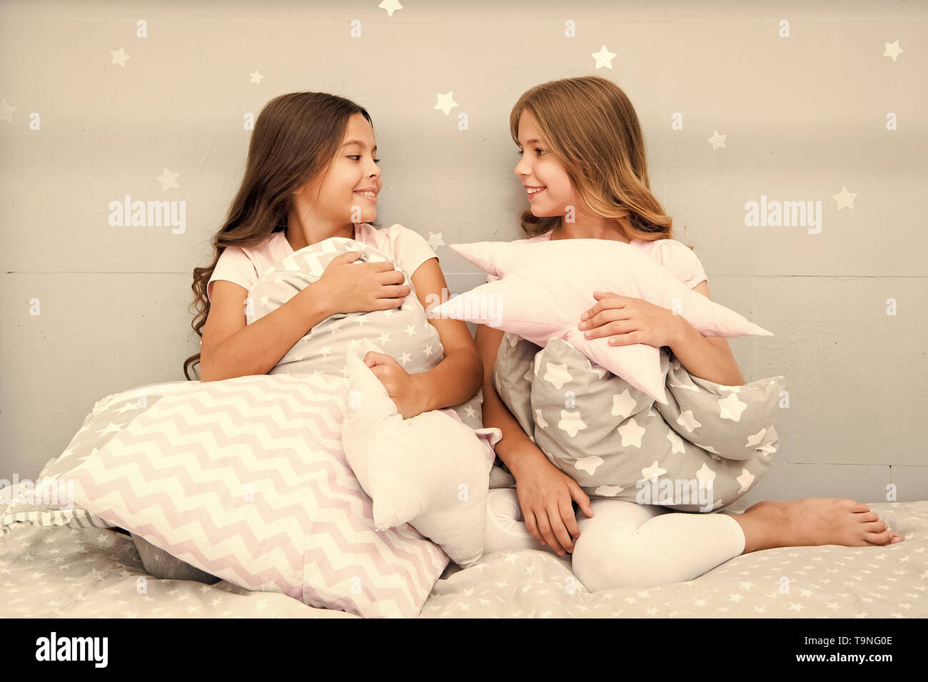 Girls children on bed with cute pillows. Pajamas party concept. Girls just want to have fun. Girlish secrets honest and sincere. Friends kids have nic - Stock Image