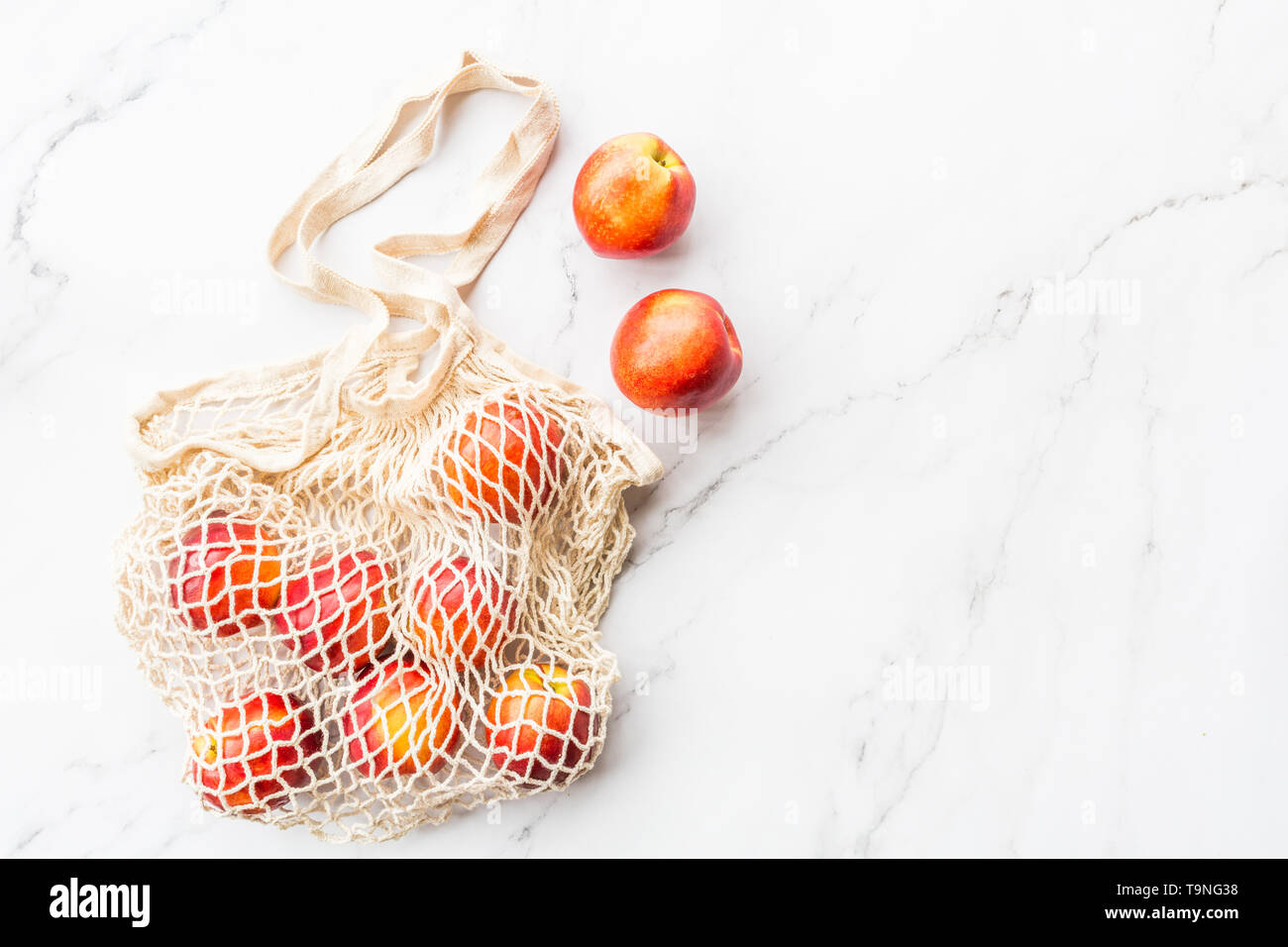 Fresh raw nectarines lying in string bag on white marble background. Flat lay, top view, summer, organic food, blogger style. Healthy concept - Stock Image