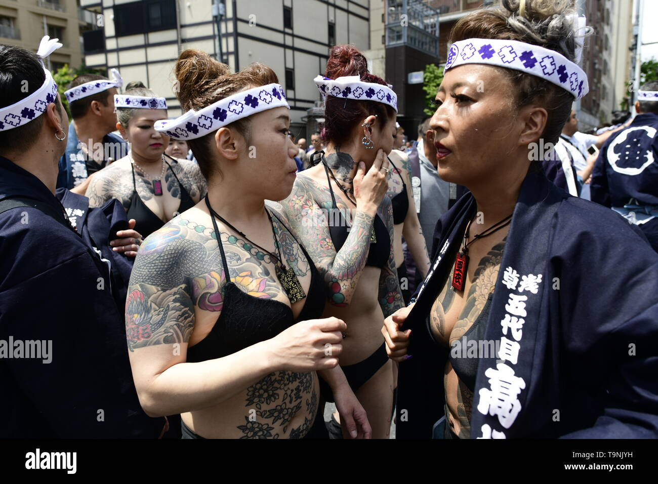 """TOKYO, JAPAN - MAY 18: Heavily tattooed Japanese women walk in the street of Asakusa during """"Sanja Matsuri"""" on May 18, 2019 in Tokyo, Japan. A boisterous traditional mikoshi (portable shrine) is carried in the streets of Asakusa to bring goodluck, blessings and prosperity to the area and its inhabitants. (Photo: Richard Atrero de Guzman/ AFLO) Stock Photo"""