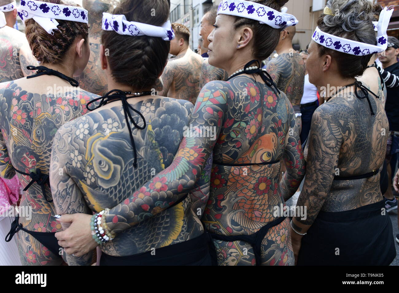 "TOKYO, JAPAN - MAY 18: Heavily tattooed Japanese women stand in the street as they wait for the portable shrine in the street of Asakusa during ""Sanja Matsuri"" on May 18, 2019 in Tokyo, Japan. A boisterous traditional mikoshi (portable shrine) is carried in the streets of Asakusa to bring goodluck, blessings and prosperity to the area and its inhabitants. (Photo: Richard Atrero de Guzman/ AFLO) Stock Photo"
