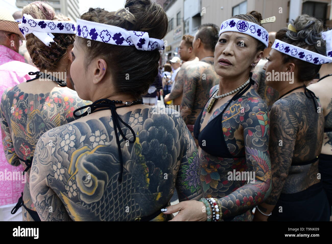 """TOKYO, JAPAN - MAY 18: Heavily tattooed Japanese women stand in the street as they wait for the portable shrine in the street of Asakusa during """"Sanja Matsuri"""" on May 18, 2019 in Tokyo, Japan. A boisterous traditional mikoshi (portable shrine) is carried in the streets of Asakusa to bring goodluck, blessings and prosperity to the area and its inhabitants. (Photo: Richard Atrero de Guzman/ AFLO) Stock Photo"""